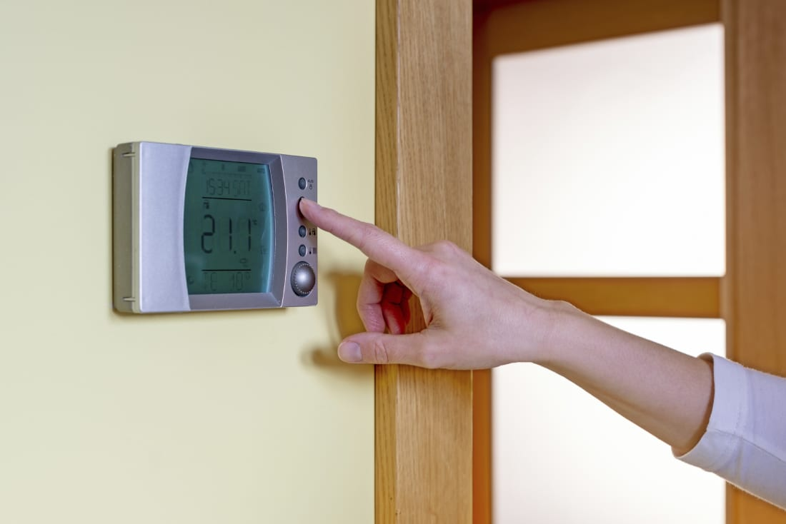 Closeup of a woman's hand setting the room temperature on a modern programmable thermostat - with copy space. Save energy and money concept