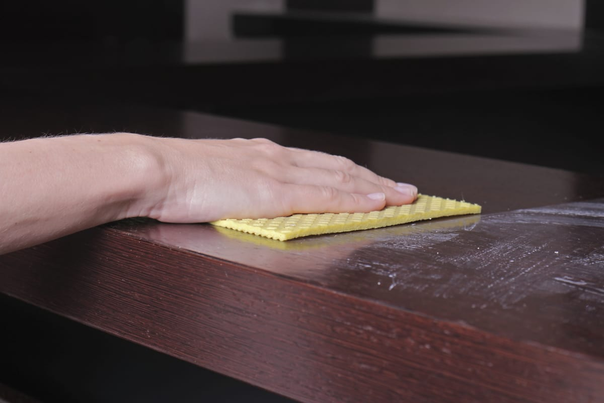 Close up of  hand cleaning wooden table with furniture polish. Using yellow sponge for cleaning dusty wood. House  cleaning and home hygiene concept