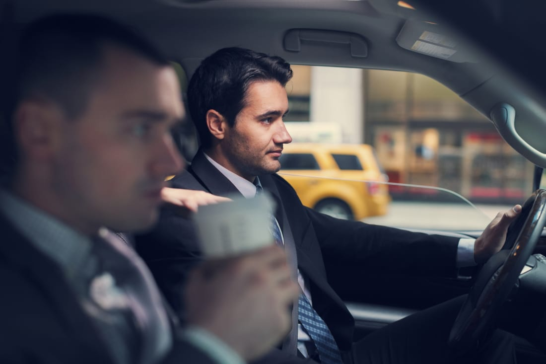 Young businessman driving a car in New York city to a business meeting with his passanger partnes who is dringing coffee. Horizontal shot inside a vehicle with visible yellow cab.