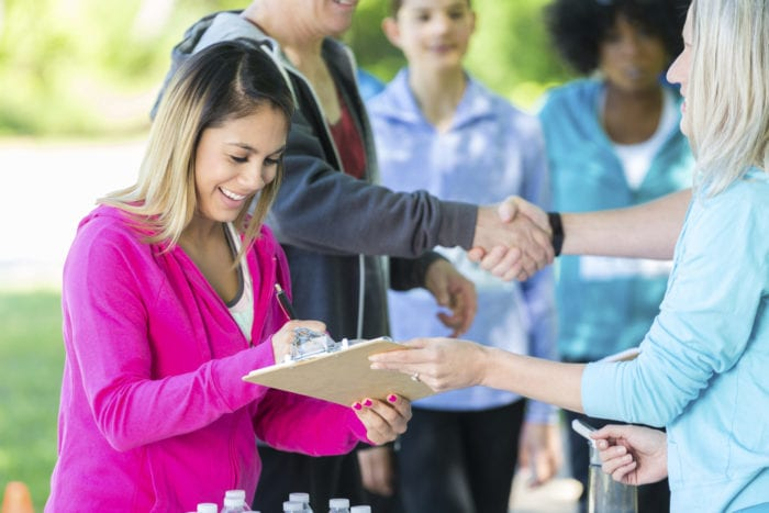 Pretty mid adult Hispanic woman signs a release form at a local charity race. A senior woman holds the clipboard as the younger woman signs the form. Diverse race participants are behind her. People are shaking hands in the background. Plastic water bottles are on the table.