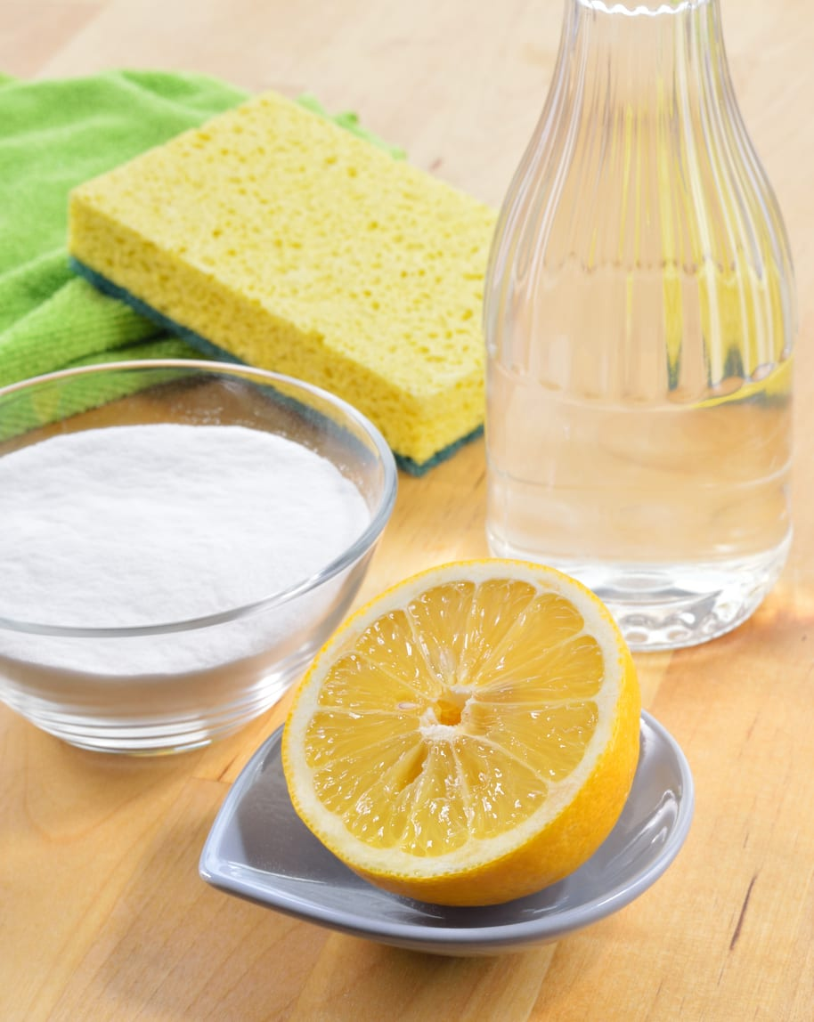 Eco-friendly natural cleaners. Vinegar, baking soda, salt, lemon and cloth on wooden table. Homemade green cleaning.