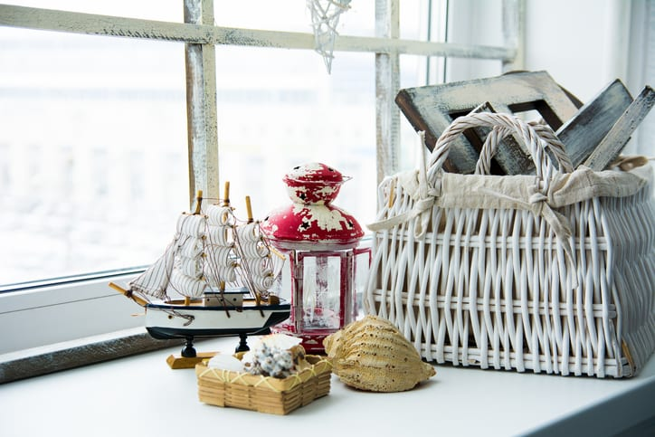 Interior windowsill in a rustic style. Ship with shells of the old lamp and a wicker basket on a windowsill.