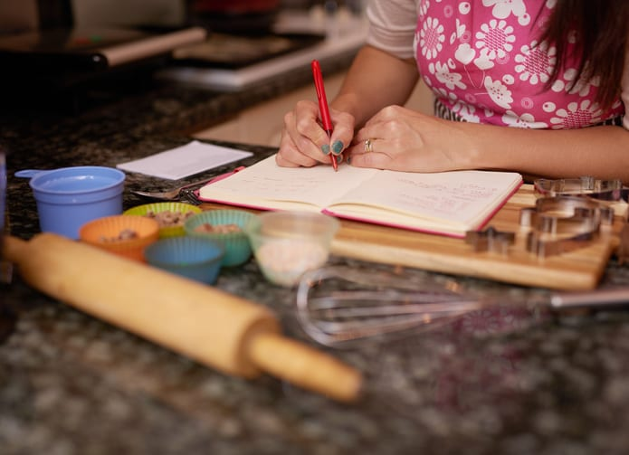 Shot of a woman writing in a recipe book